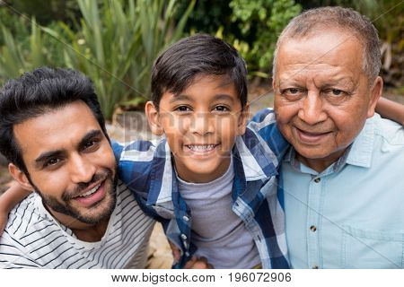 Close up portrait of family with arm around at park