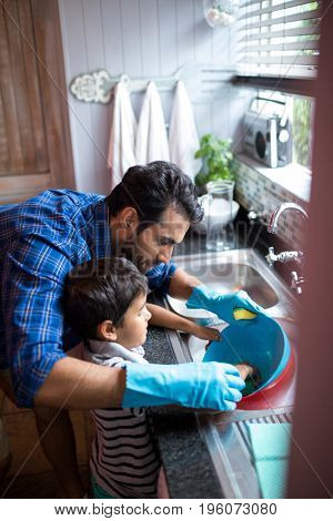 High angle view of father assisting son for cleaning utensils at home