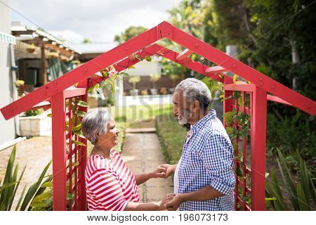 High angle view of couple holding hand while standing by metallic structure in yard