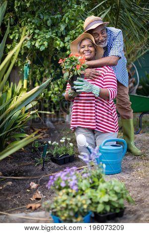 Man embracing woman kneeling on field during gardening in yard