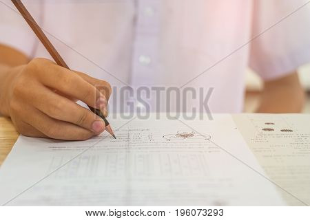 Blurred of Asian boy students hand holding pencil writing fill in Exams paper sheet or test papers Mathematics on wood desk table with student uniform in exam class room education concept