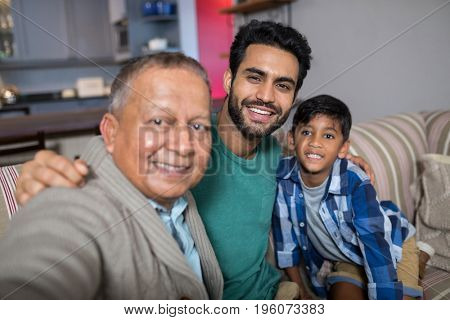 Close up of smiling family with arm around sitting on sofa at home
