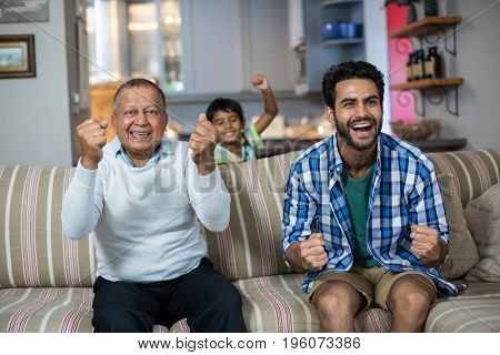 Cheerful family clenching fist while watching soccer match at home