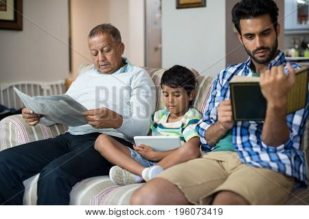 Boy with grandfather and father sitting on sofa in living room at home