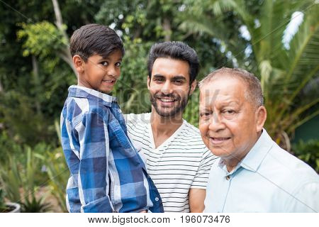Portrait of father carrying son while standing by senior man at home