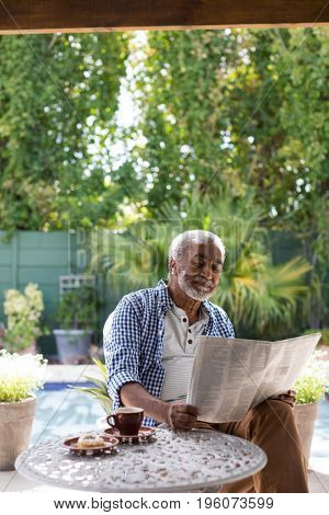 Smiling senior man reading newspaper while sitting at table in yard