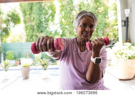 Close up portrait of woman exercising with dumbbell while sitting in yard