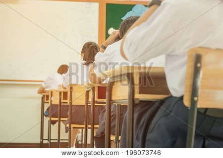 Asian girl students in uniform attending examination in classroom educational view of college people having exams and test in seat rows at exam class room at high school education concept