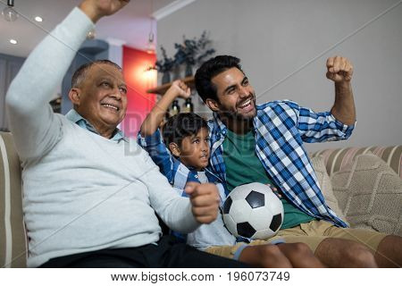 Happy family with arms raised watching soccer match while sitting on sofa at home