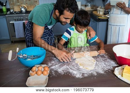 High angle view of father assisting son for rolling dough with man background