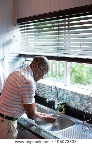 Side view of man washing hands in sink by window at home