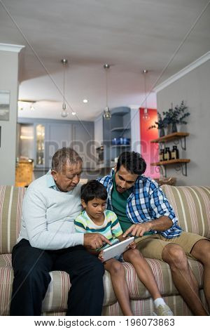 Boy using tablet while sitting with father and grandfather on sofa in living room at home