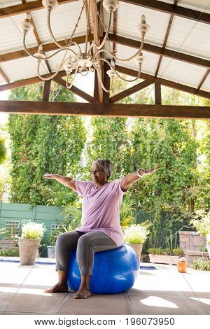Full length senior woman with arms outstretched sitting on exercise ball under shed in yard
