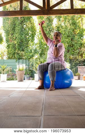 Senior woman exercising with dumbbells while sitting on fitness ball