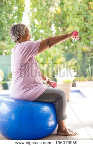 Side view of senior woman lifting dumbbells while sitting on fitness ball in yard