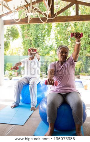 Full length of senior couple exercising with dumbbells while sitting on fitness ball in yard