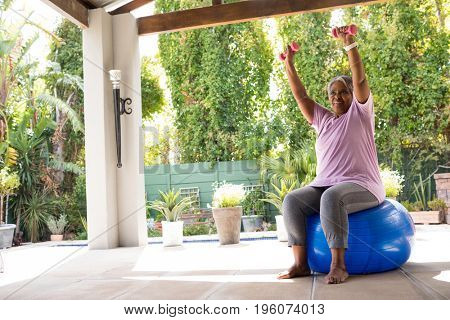 Woman with arms raised holding dumbbells while sitting on fitness ball