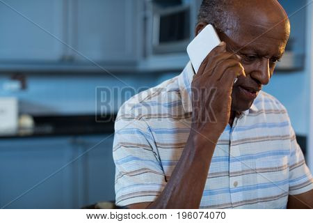 Close up of man talking on mobile phone in kitchen at home