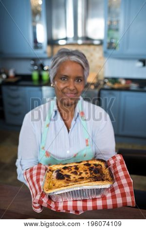 Portrait of senior woman showing baked food while standing in kitchen at home