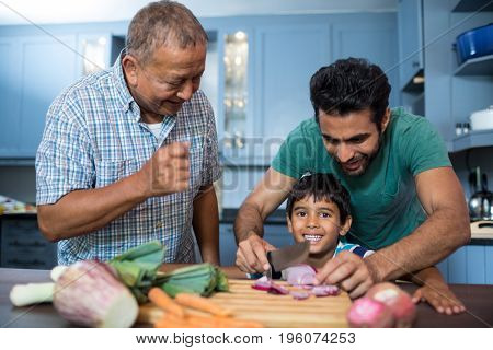 Man looking at boy cutting onion with father in kitchen at home