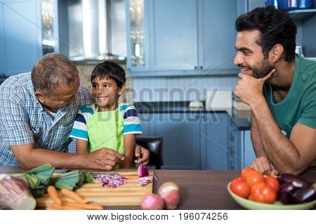 Man looking at happy boy and grandfather while preparing food
