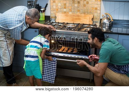 Family keeping cookies in oven at home