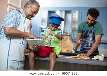Grandfather showing tablet to grandson with man rolling dough in background