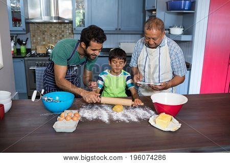 Father assisting son for preparing food while standing by man using tablet in kitchen at home