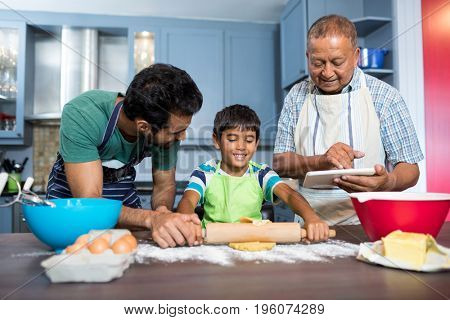 Smiling man using table while standing by father and son preparing food in kitchen at home