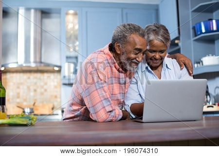 Smiling couple using laptop computer in kitchen at home