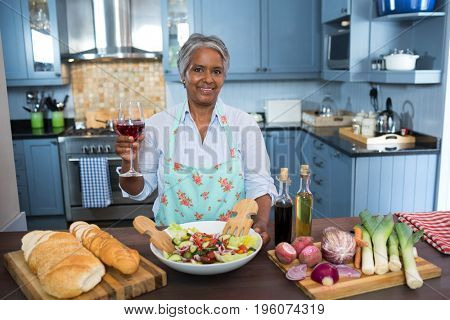 Portrait of woman holding wineglass while standing by table in kitchen at home