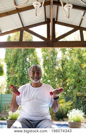 Smiling man holding dumbbells while exercising under shed at yard
