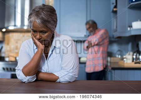 Sad woman with man in background at home