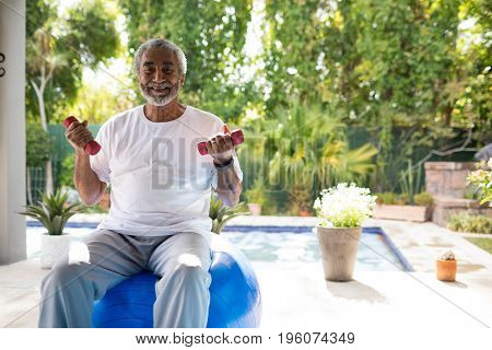 Portrait of man holding dumbbells while sitting on fitness ball in yard