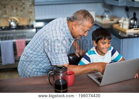 High angle view of grandfather assisting grandson using laptop in kitchen at home