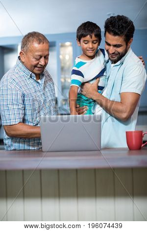 Father carrying son while standing with man at home