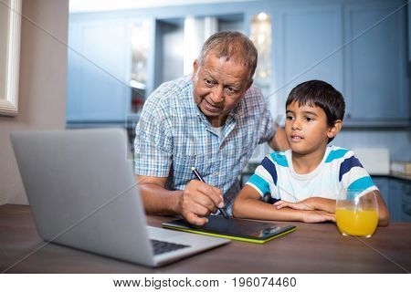 Man writing on tablet while using laptop with grandson at table at home