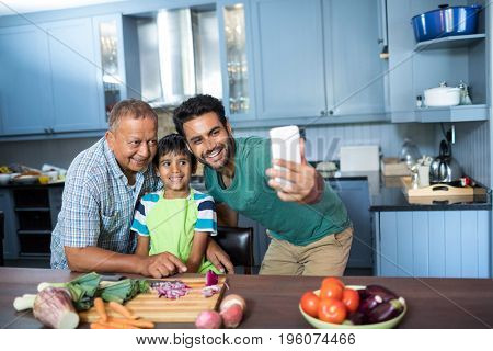 Family taking selfie while preparing food in kitchen at home
