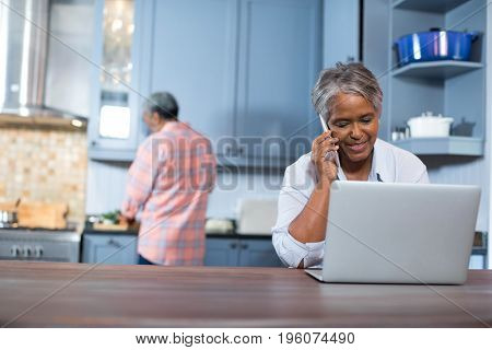 Woman talking on phone while using laptop in kitchen at home