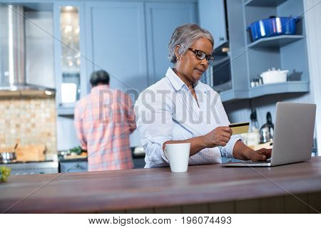 Woman holding credit card while using laptop in kitchen at home
