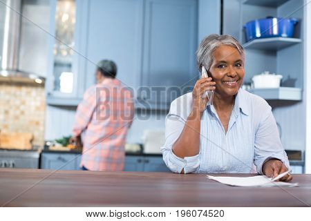 Portrait of smiling woman talking phone while standing in kitchen at home