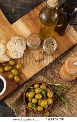 High angle view of olives and oils bottles with bread on cutting board at table