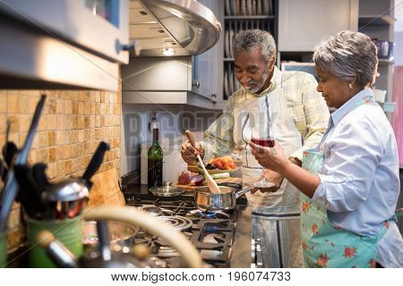 Senior couple preparing food in kitchen at home