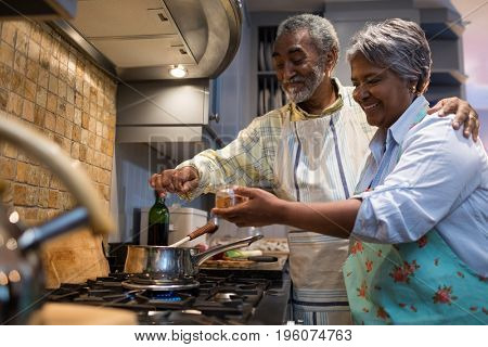 Smiling senior couple preparing food while standing in kitchen at home