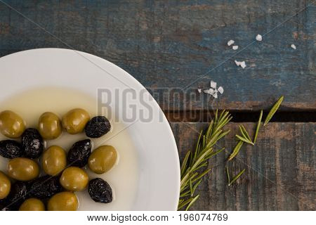 Close up of olives in plate with oil on wooden table