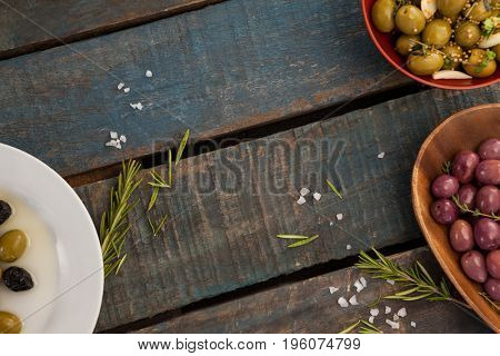 Overhead view of olives with herbs and spices in container on wooden table