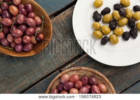 Overhead view of olives in bowls and plate on wooden table
