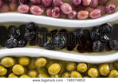 Close-up of various pickled olives in platter