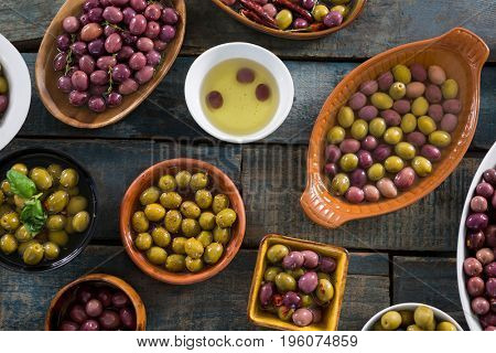 Pickled olives in bowl on wooden table