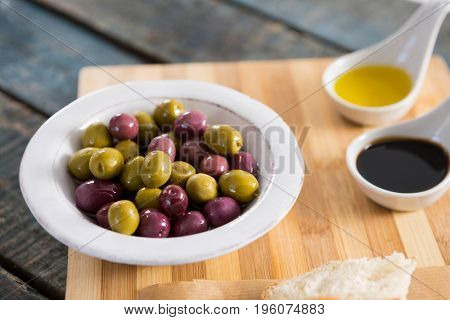 Close-up of marinated olives with olive oil on chopping board
